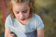 Het kleine schoolmeisje schreeuwt over een schoolnotitieboekje Royalty-vrije Stock Fotografie