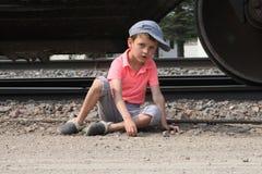 Het kleine stadsjongen spelen dichtbij treinsporen stock foto