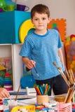 Het kleine studentenjongen schilderen in kunstacademieklasse Royalty-vrije Stock Afbeelding