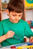 Het kleine studentenjongen schilderen in kunstacademieklasse Stock Foto's