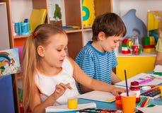 Het kleine van de studentenmeisje en jongen schilderen in kunstacademieklasse Stock Afbeeldingen