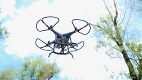 Het kleine verblijf van de quadcopterhommel in lucht, vier kleine propellers spint snel, hemel en bomen op achtergrond Populair m stock video