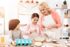 Het kleine vrolijke meisje slaat eieren in keuken De grootmoeder giet melk in kom royalty-vrije stock foto's