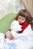 Het kleine zieke meisje met sjaal omhelst stuk speelgoed draagt Royalty-vrije Stock Afbeelding