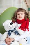 Het kleine zieke meisje met sjaal omhelst stuk speelgoed draagt Stock Foto