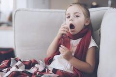 Het kleine zieke meisje zit op een witte die laag in een rode sjaal wordt verpakt Zij bespat haar keel met een geneeskrachtige ne royalty-vrije stock afbeelding