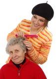 Het kleinkind borstelt een grootmoeder Stock Afbeeldingen