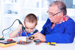 Het kleinkind die van het grootvaderonderwijs met soldeerbout werken Stock Fotografie