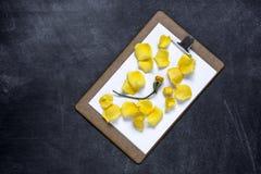 Het klembord met en aPetals van geel namen op zwarte achtergrond toe V Royalty-vrije Stock Fotografie