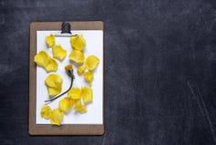 Het klembord met en aPetals van geel namen op zwarte achtergrond toe V Stock Afbeelding
