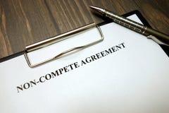 Het klembord met niet-concurreert overeenkomst en pen op bureau royalty-vrije stock fotografie
