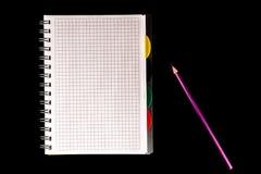 het het kleurenpotlood en notitieboekje, isoleren op zwarte achtergrond stock afbeeldingen
