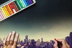 Het kleurpotloodkleur van de handholding, die op bord, met dubbele de meningsachtergrond van de blootstellings panoramische stad  Royalty-vrije Stock Foto