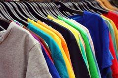 Het kleurrijke de stof van winkeloverhemden hangen op een rek Stock Afbeeldingen