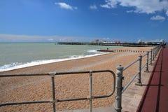 Het kleurrijke die strand van Hastings met de Pijler en open aan publiek in 2016 op de achtergrond en een blauwe hemel met aardig Royalty-vrije Stock Foto