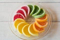 Het kleurrijke die suikergoed van de fruitgelei in cirkel op houten lijst wordt geschikt Stock Foto's