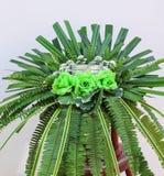 Het kleurrijke groene kunstbloemenboeket nam, varenbladeren en palm op witte concrete muurachtergrond toe stock afbeeldingen