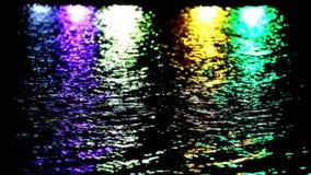 Het kleurrijke licht overdenkt het water bij nacht stock videobeelden