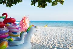 Het kleurrijke opblaasbare drijven op het strand stock foto