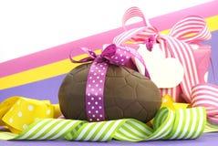 Het kleurrijke roze, gele en purpere thema van thema Gelukkige Pasen met chocoladeei en giftdoos Stock Afbeelding
