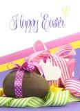 Het kleurrijke roze, gele en purpere thema van thema Gelukkige Pasen met chocoladeei en giftvakje met steekproeftekst Stock Foto's