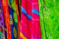 Het kleurrijke Sarongs-hangen door een strand Stock Foto's