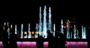 Het kleurrijke schot van de waterfontein bij nacht met mensensilhouetten op voorgrond royalty-vrije stock fotografie