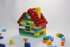 Het kleurrijke stuk speelgoed huis met bakstenen knoeit binnen stock afbeeldingen