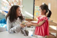 Het kleuterschoolschoolmeisje die een gift geven aan haar vrouwelijke leraar in een klaslokaal, zijaanzicht, sluit omhoog royalty-vrije stock foto's