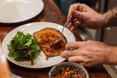 Het kleven van de saus van tomatensalsa op een toost door lepel met plantaardige salade stock foto