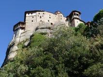 Het klooster streek hoog omhoog op de rotsen in Meteora, Griekenland hierboven wordt gezien die neer van Stock Afbeelding