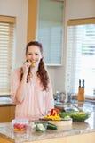 Het knagen aan van de vrouw groene paprika terwijl het voorbereiden van gezonde salade Stock Fotografie