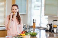 Het knagen aan van de vrouw groene paprika terwijl het voorbereiden van salade Royalty-vrije Stock Foto