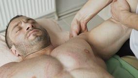 Het knappe atleet ontspannen op therapie van het masseren van triceps 4K stock footage