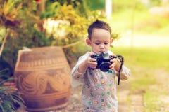 Het knappe Aziatische jonge geitje neemt een foto door DSLR camera royalty-vrije stock fotografie
