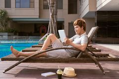 Het knappe Aziatische mens ontspannen door pool en het lezen eBook royalty-vrije stock fotografie