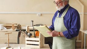 Het knappe bejaarde maakt nota's in de blocnote in de workshop stock footage