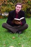 Het knappe boek van de mensenlezing op een gras in de herfst Stock Afbeeldingen