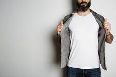 Het knappe brutale gebaarde hipstermodel stelt in zwart jeansoverhemd en leeg wit de zomerkatoen van de t-shirtpremie, op wit royalty-vrije stock afbeeldingen