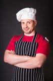 Het knappe chef-kok stellen tegen zwarte achtergrond Royalty-vrije Stock Afbeeldingen