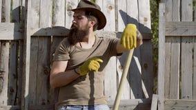 Het knappe gebaarde landbouwer werken met schoffelt op de lentegebied Retro reclame van alcoholische dranken Groen grasgebied stock videobeelden