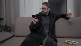 Het knappe gebaarde mens ontspannen op bank stock videobeelden