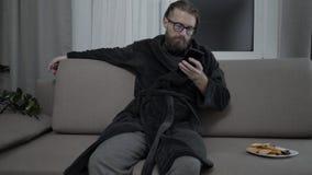Het knappe gebaarde mens ontspannen op bank stock video