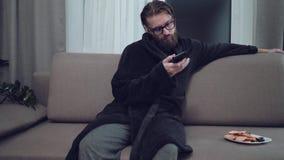 Het knappe gebaarde mens ontspannen op bank stock footage
