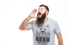 Het knappe gebaarde mens schreeuwen luid met hand dichtbij mond stock foto's