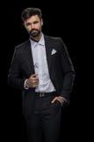 Het knappe gebaarde zakenman stellen in zwart kostuum Royalty-vrije Stock Fotografie