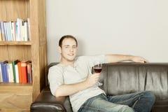 Het knappe gelukkige mens ontspannen met een glas wijn stock foto's