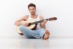 Het knappe gitaarspeler praktizeren Royalty-vrije Stock Afbeeldingen