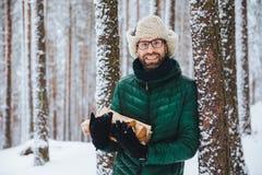 Het knappe glimlachende mannetje draagt warme de winterkleren houdt brandhout, bevindt zich dichtbij boom, doorbrengt vrije tijd  royalty-vrije stock foto's