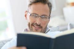 Het knappe het boek van de mensenlezing genieten van op middelbare leeftijd Stock Fotografie